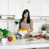 A mulher que cozinha vegetais frutifica alimento saudável simples da cozinha home Fotografia de Stock