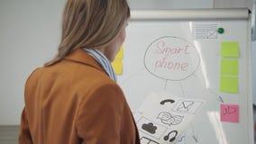 Mulher que cria o protótipo para o programa novo do Web site ou o app móvel vídeos de arquivo