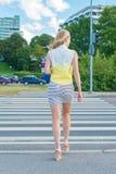 Mulher que cruza a estrada Imagens de Stock