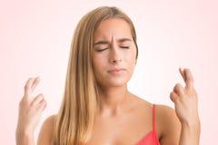 Mulher que cruza seus dedos para a boa sorte Fotos de Stock Royalty Free
