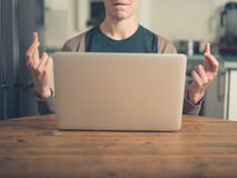 Mulher que cruza seus dedos pelo portátil Imagens de Stock Royalty Free