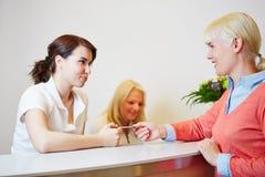 Mulher que dá a carta inteligente ao recepcionista Imagem de Stock