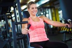 Mulher que dá certo no gym na máquina imagens de stock
