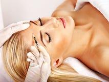 Mulher que dá injeções do botox. Imagens de Stock