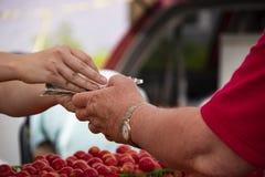 Mulher que dá a mudança do homem para a compra no mercado dos fazendeiros - mãos somente - foco seletivo fotos de stock royalty free