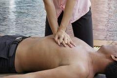 Mulher que dá o CPR a afogar o homem, poupanças de vida do CPR Imagens de Stock Royalty Free