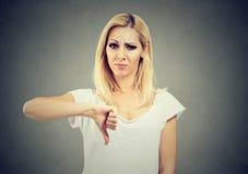A mulher que dá o polegar gesticula para baixo a vista com expressão e desaprovação negativas Imagem de Stock