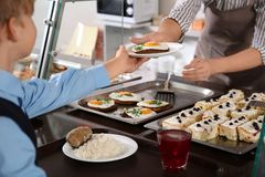 Mulher que dá a placa com alimento saudável ao menino na cantina da escola imagem de stock royalty free