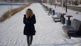 Mulher que dá uma volta ao longo do passeio no banco do rio no inverno filme
