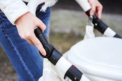 Mulher que d? uma volta com beb?-transporte Feche acima das mãos fêmeas mudam o bebê-transporte ajustável do punho imagens de stock royalty free