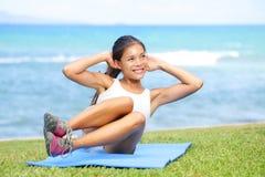 A mulher que da aptidão exercitar se senta levanta fora Fotografia de Stock Royalty Free