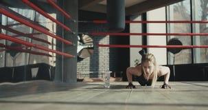 A mulher que da aptidão fazer empurra levanta na esteira do exercício Fêmea nova saudável que dá certo no estúdio filme