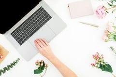 Mulher que datilografa no portátil Espaço de trabalho com mãos fêmeas, portátil, caderno e as flores cor-de-rosa no fundo branco  imagem de stock royalty free