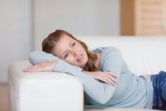 Mulher que daydreaming no sofá fotografia de stock