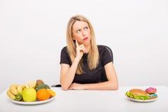 Mulher que decide entre alimentos saudáveis e insalubres Imagens de Stock