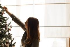 Mulher que decora a árvore de Natal Imagem de Stock
