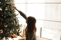 Mulher que decora a árvore de Natal Foto de Stock