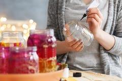 Mulher que decora frascos Fotografia de Stock Royalty Free