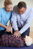 Mulher que demonstra o CPR no manequim do treinamento na classe dos primeiros socorros imagem de stock