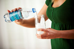 Mulher que derrama a água de Dasani no vidro do gelo Fotografia de Stock Royalty Free