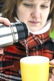 Mulher que derrama a água quente da garrafa de garrafa térmica ao copo Imagem de Stock Royalty Free