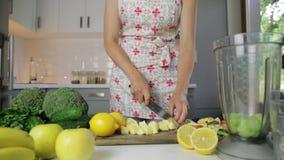 Mulher que desbasta vegetais verdes para o batido da desintoxicação em casa Comer saud?vel, alimento do vegetariano, fazendo diet vídeos de arquivo