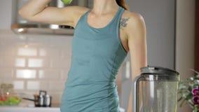 Mulher que desbasta vegetais verdes para o batido da desintoxicação em casa Comer saud?vel, alimento do vegetariano, fazendo diet video estoque