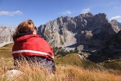 Mulher que descansa e que olha os picos de montanha Foto de Stock Royalty Free