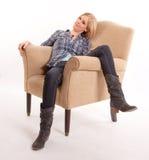 Mulher que descansa em uma poltrona Foto de Stock Royalty Free