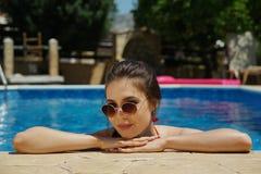 Mulher que descansa na piscina fotos de stock