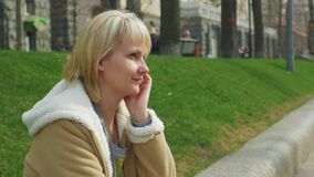 Mulher que descansa na primavera o parque, falando no telefone video estoque