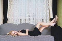Mulher que descansa no sofá Imagem de Stock Royalty Free