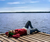 Mulher que descansa perto do lago Foto de Stock Royalty Free