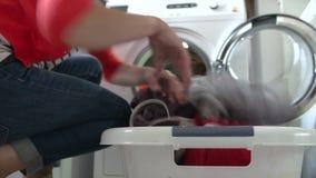 Mulher que descarrega a roupa da máquina de lavar vídeos de arquivo
