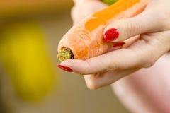 Mulher que descasca o vegetal da cenoura imagem de stock royalty free