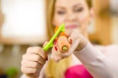 Mulher que descasca o vegetal da cenoura foto de stock