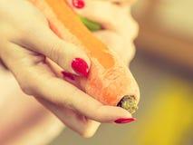 Mulher que descasca o vegetal da cenoura fotografia de stock royalty free