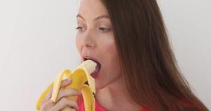 Mulher que descasca uma banana e que come o fundo branco vídeos de arquivo