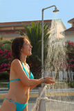 Mulher que desgasta no chuveiro azul das tomadas do terno de banho Imagem de Stock
