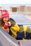 Mulher que desgasta nos mittens e nas mentiras da manta no lounger Foto de Stock Royalty Free