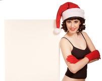Mulher que desgasta o painel de anúncio próximo do chapéu de Santa Fotos de Stock Royalty Free