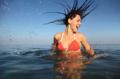 Mulher que desgasta o terno de banho vermelho que gira no mar Imagem de Stock