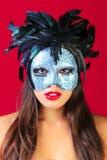 Mulher que desgasta um fundo do vermelho da máscara do disfarce foto de stock royalty free