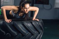 A mulher que desportiva apta fazer empurra levanta no conceito do treinamento do poder da força do pneu imagens de stock