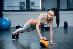 a mulher que desportiva nova fazer empurra levanta com uma mão na bola fotografia de stock royalty free