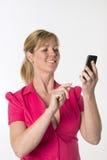 Mulher que disca um número em um telefone celular Fotografia de Stock