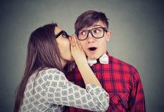 Mulher que diz a bisbolhetice secreta de sussurro na orelha a um homem chocado surpreendido fotografia de stock