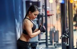 A mulher que dobra o braço muscles na máquina do cabo no gym Fotos de Stock
