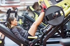 Mulher que dobra os músculos na máquina da imprensa do pé no gym imagens de stock royalty free