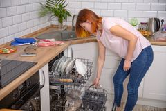 Mulher que dobra os pratos na máquina de lavar louça Fêmea na cozinha housework fotos de stock royalty free